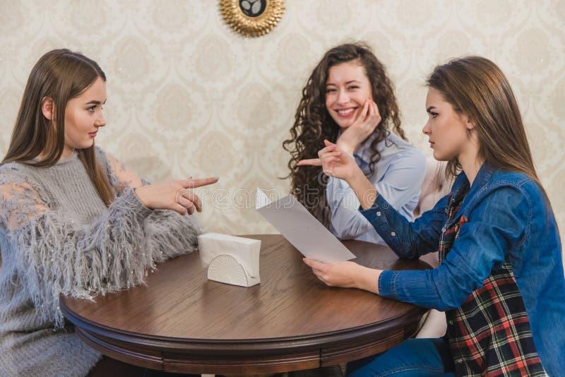 Drie leuke meisjes zitten in een koffiewinkel en kiezen orden Tegelijkertijd het babbelen glimlach Drie brunettes met royalty-vrije stock fotografie
