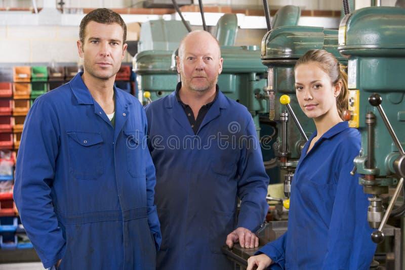 Drie machinisten in werkruimte door machine royalty-vrije stock afbeeldingen