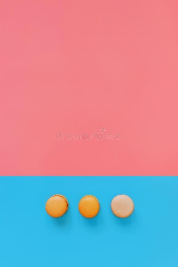 Drie makarons op een roze blauwe achtergrond royalty-vrije stock afbeelding