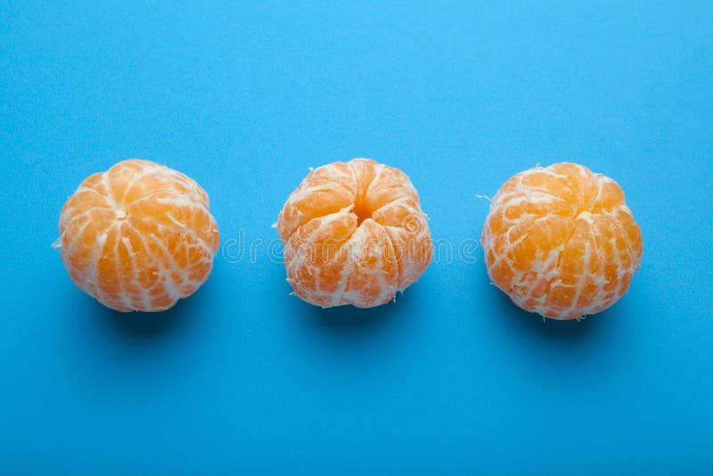 Drie mandirins zonder schil op een blauwe achtergrond royalty-vrije stock afbeeldingen