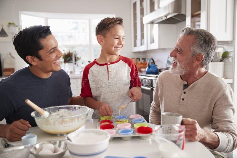 Drie mannelijke generaties die van familie cakes maken samen bij de lijst in de keuken, sluiten omhoog royalty-vrije stock fotografie