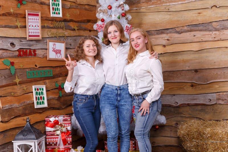 Drie meisjes bevinden zich gelukkig dichtbij de Kerstboom en de glimlach Het concept een vakantie royalty-vrije stock foto