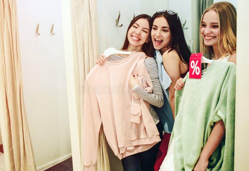 Drie meisjes bevinden zich in kleedkamer en het lachen De Aziatische vrouw houdt roze sweatshirt en probeert het op zich royalty-vrije stock foto