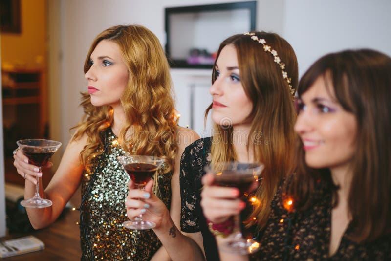 Drie meisjes bij een partij met dranken in hun handen, nadruk op royalty-vrije stock afbeeldingen