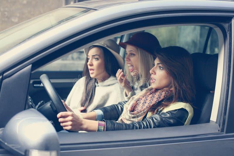 Drie meisjes in de auto Meisjes die in de betrokken auto zitten royalty-vrije stock afbeelding