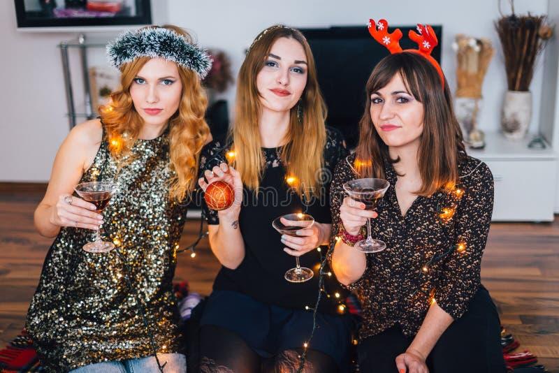 Drie meisjes die bij een huispartij stellen stock afbeeldingen