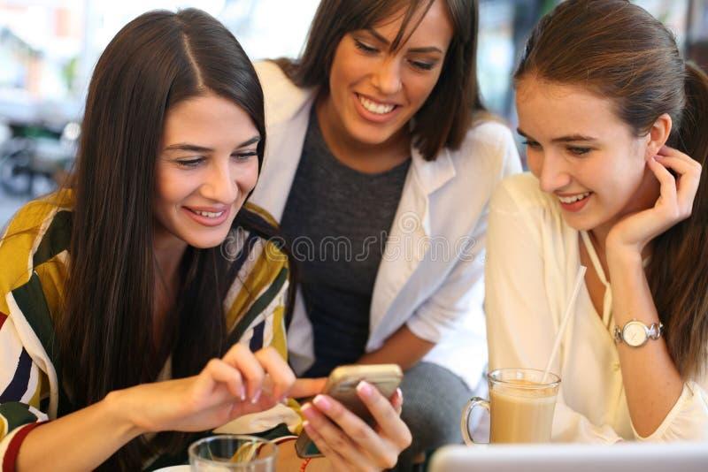 Drie meisjes die bij koffie zitten huisvesten het gebruiken van slimme telefoon en stock foto