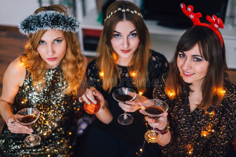 Drie meisjes die camera bij een huispartij bekijken stock foto