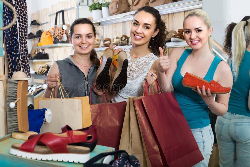 Drie meisjes die document het winkelen zakken in de boutique houden royalty-vrije stock foto