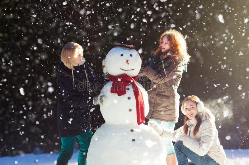 Drie meisjes die een sneeuwman bouwen royalty-vrije stock fotografie