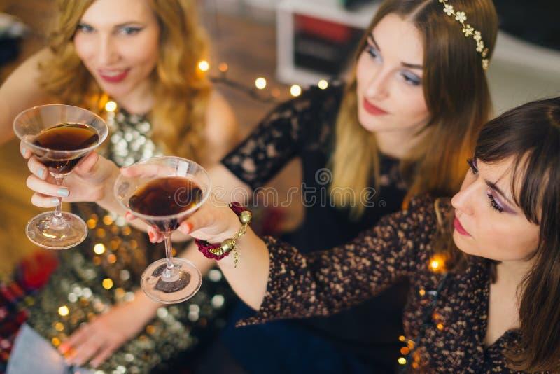 Drie meisjes die een toost voor Nieuwjaar` s Vooravond hebben, nadruk op glas royalty-vrije stock afbeeldingen