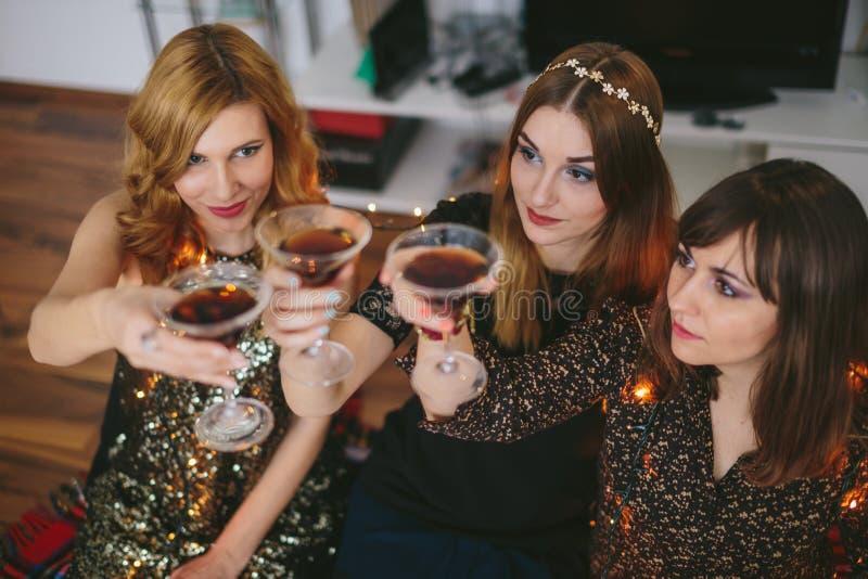 Drie meisjes die een toost voor Nieuwjaar` s Vooravond hebben, nadruk op het meisje stock foto