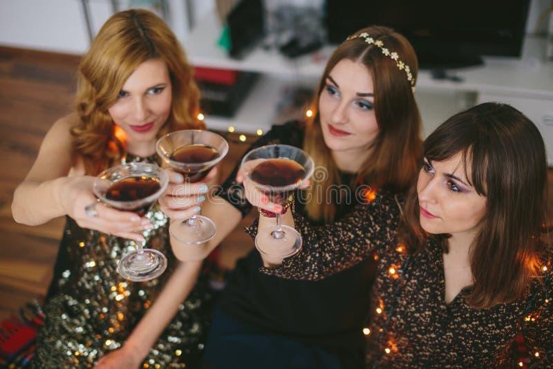 Drie meisjes die een toost voor Nieuwjaar` s Vooravond hebben, nadruk op het meisje royalty-vrije stock foto's