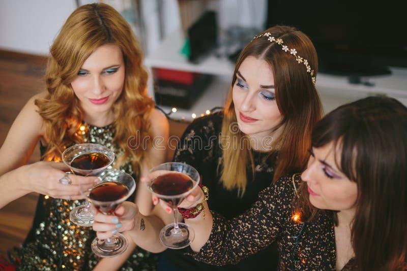 Drie meisjes die een toost voor Nieuwjaar` s Vooravond hebben, nadruk op het meisje stock foto's