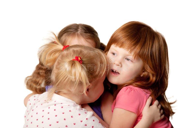 Drie meisjes die geheimen delen stock fotografie