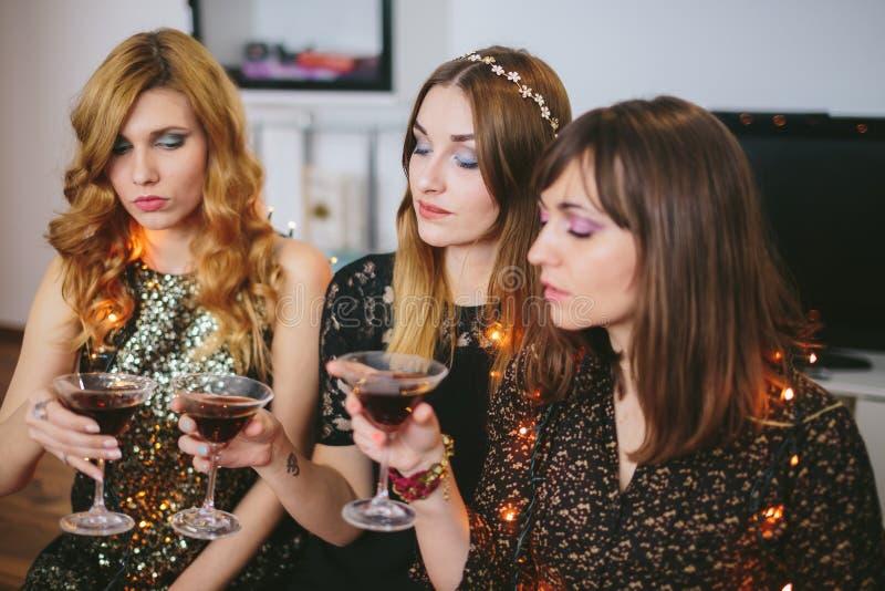 Drie meisjes die hun dranken bij een partij, nadruk op het meisje controleren stock afbeelding