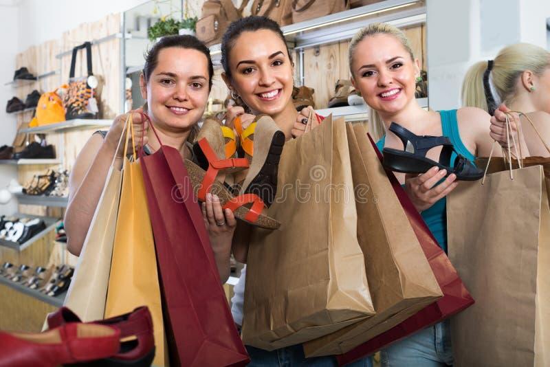 Drie meisjes die samen winkelen stock foto