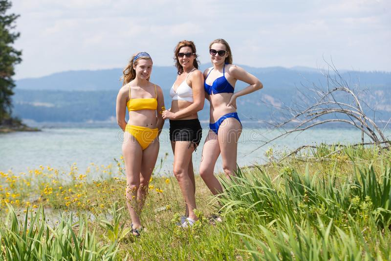 Drie meisjes die zon krijgen bij een meer royalty-vrije stock afbeeldingen