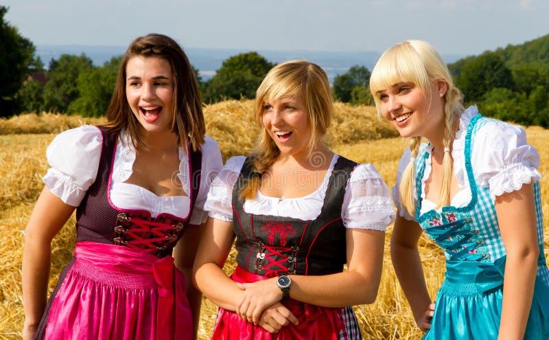 Drie meisjes in Dirndl stock afbeeldingen