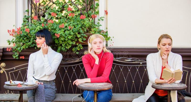 Drie meisjes doen verschillende dingen verschillende manieren te ontspannen Meisjes in koffie Sociale diversiteit Het luisteren m royalty-vrije stock afbeelding