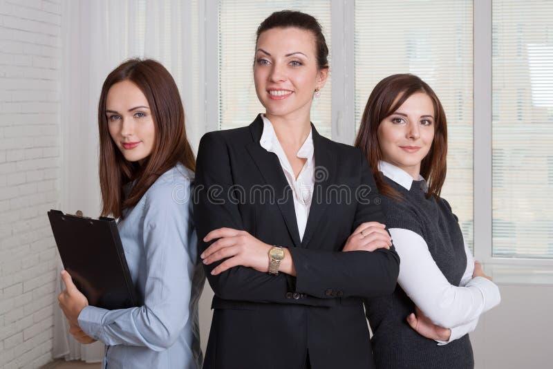 Drie meisjes in formele kleding zijn van verschillende hoogten stock afbeeldingen