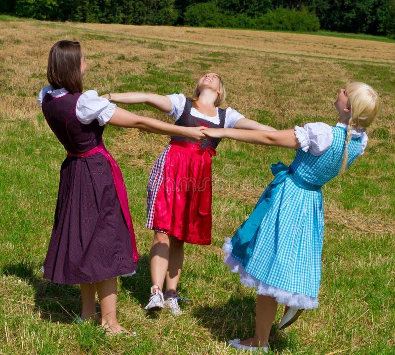Drie meisjes in het dansen Dirndl royalty-vrije stock fotografie
