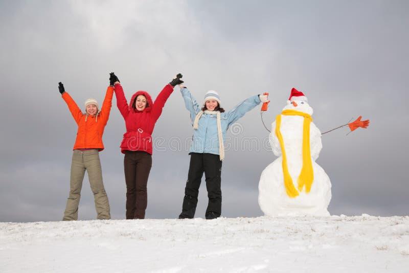 Drie meisjes met sneeuwman royalty-vrije stock afbeeldingen
