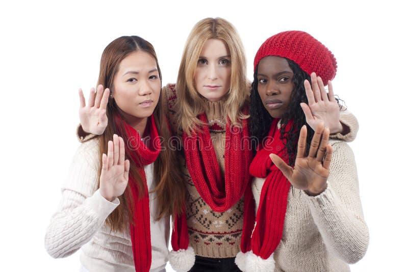 Drie meisjes met verschillende afleiding houden hun indient stock afbeeldingen