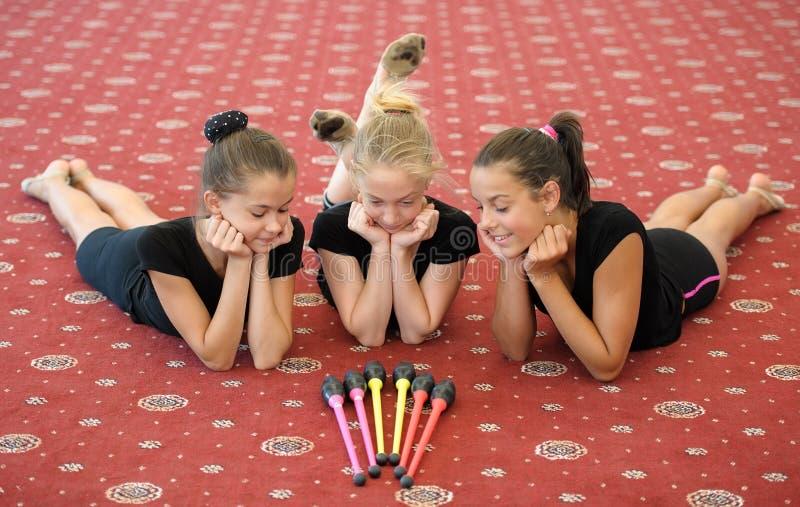 Drie meisjes op de vloer die Indische clubs bekijkt royalty-vrije stock foto