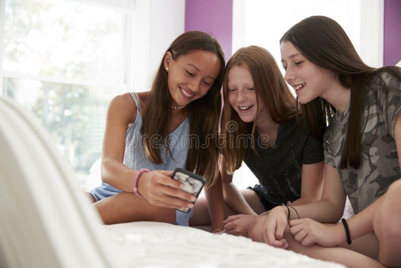 Drie meisjes op een bed die een smartphone gebruiken, sluiten omhoog royalty-vrije stock afbeeldingen