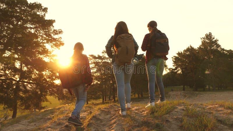 Drie meisjes reizen, lopen door hout om heuvel te beklimmen verheugen zich en opheffen hun handen tot de bovenkant Wandelaarmeisj royalty-vrije stock foto