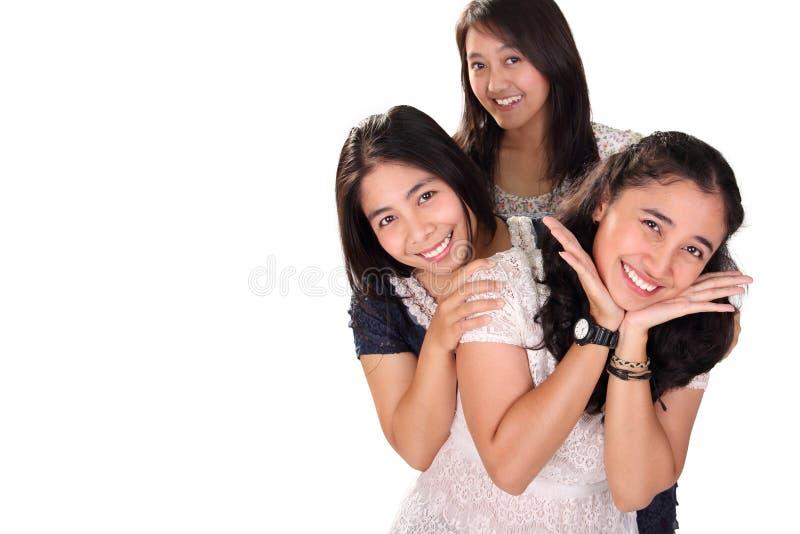 Drie meisjes stellen samen over witte exemplaarruimte stock fotografie