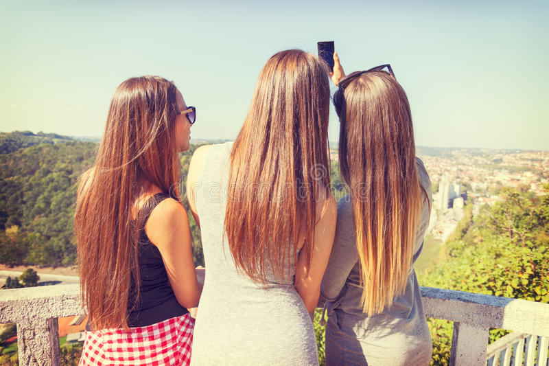 Drie meisjes van achter in openlucht het nemen selfie stock foto's
