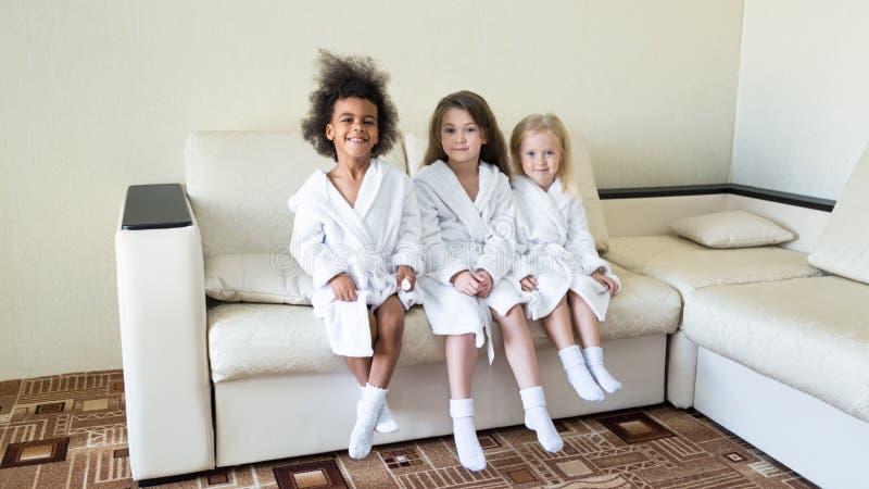 Drie meisjes van verschillende nationaliteiten zitten op de laag stock afbeelding