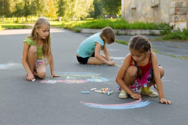 Drie meisjesjonge geitjes die absorbedly krijt trekken op de bestrating royalty-vrije stock afbeeldingen