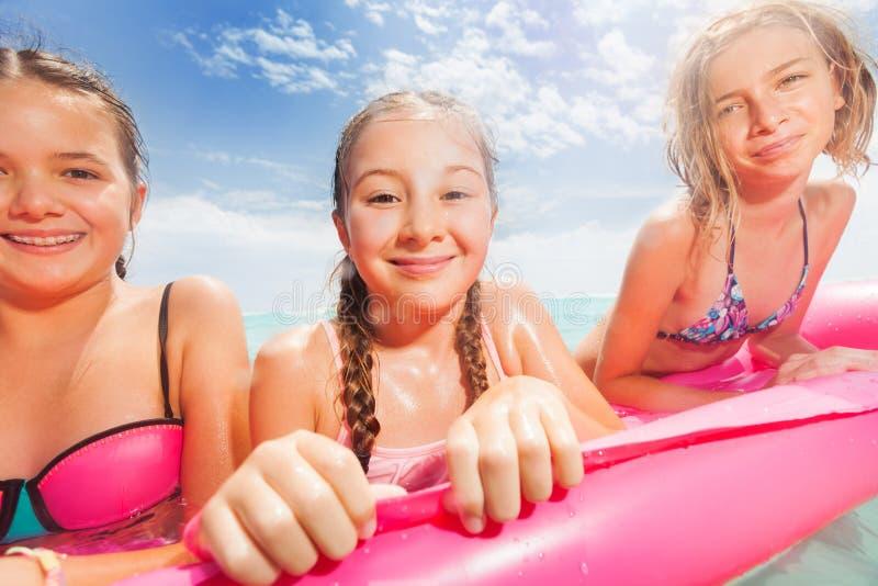 Drie meisjesportret op het strand matrass stock foto