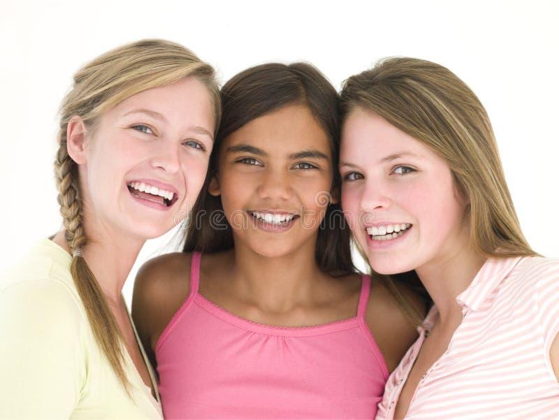 Drie meisjesvrienden die samen glimlachen stock foto