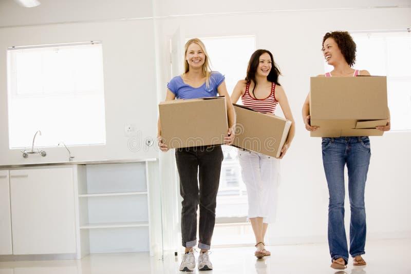 Drie meisjesvrienden die zich in het nieuwe huis glimlachen bewegen royalty-vrije stock afbeelding
