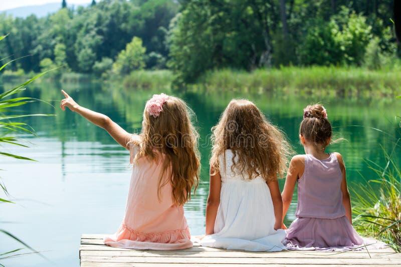 Drie meisjesvrienden samen op rivierpier. stock foto's