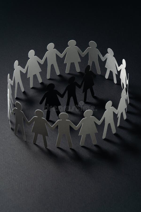 Drie menselijke die document cijfers door cirkel van document mensen worden omringd die handen op donkere oppervlakte houden Bull stock fotografie