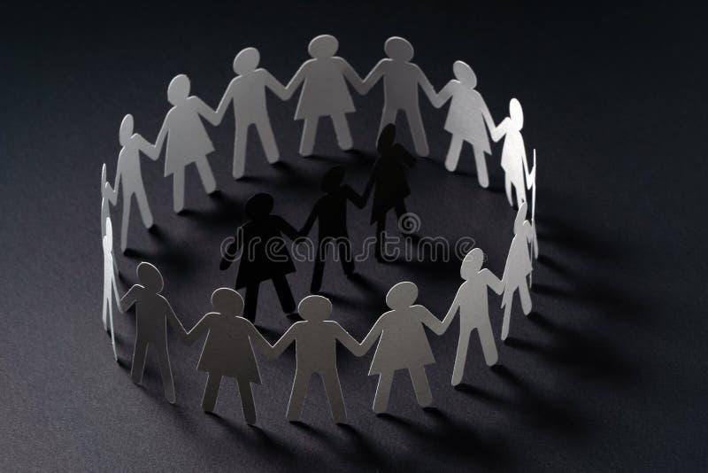 Drie menselijke die document cijfers door cirkel van document mensen worden omringd die handen op donkere oppervlakte houden Bull royalty-vrije stock afbeelding