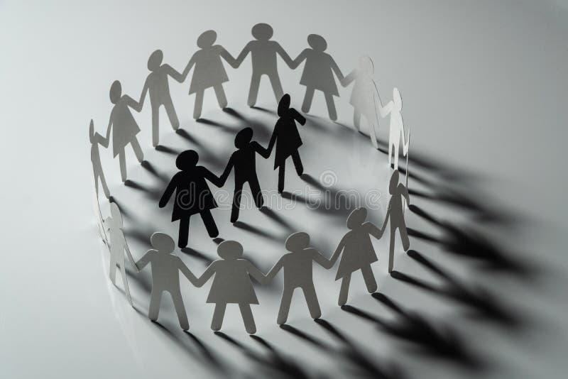 Drie menselijke die document cijfers door cirkel van document mensen worden omringd die handen op witte oppervlakte houden Bullin stock afbeeldingen