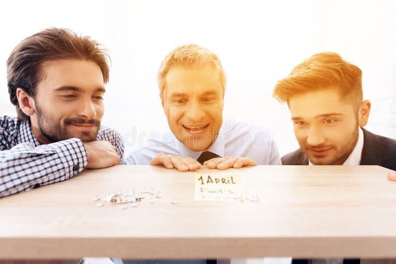 Drie mensen bekijken de administratieve knopen die op de lijst liggen stock fotografie