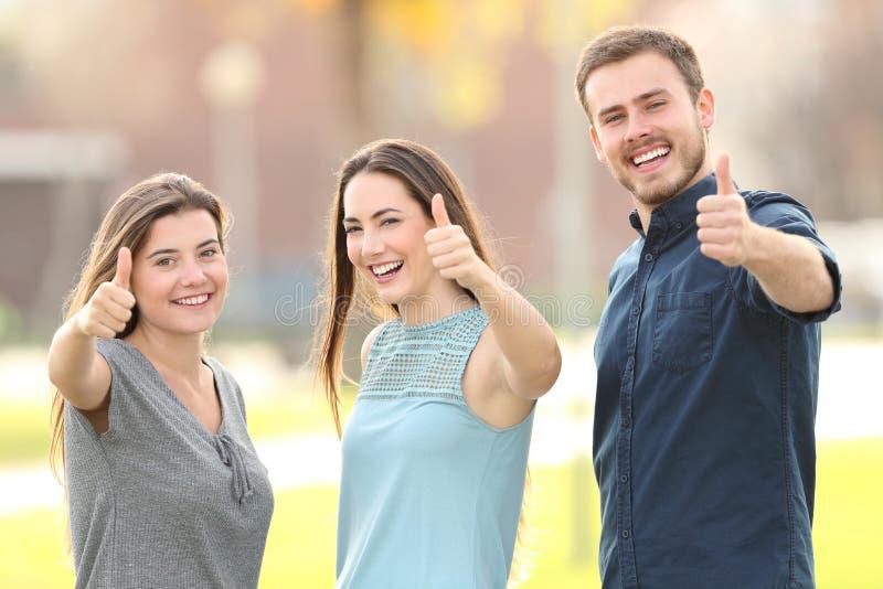 Drie mensen die duimen omhoog in de straat gesturing stock foto's