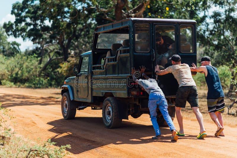 Drie mensen die een auto duwen die in het zand in savanne plakte stock afbeelding