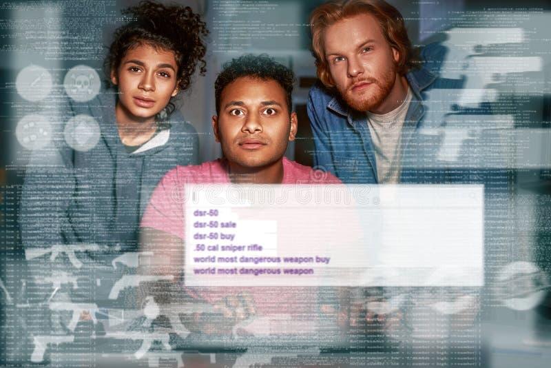 Drie mensen die geheime informatie zoeken in darknet Kijk aan het scherm royalty-vrije stock afbeelding