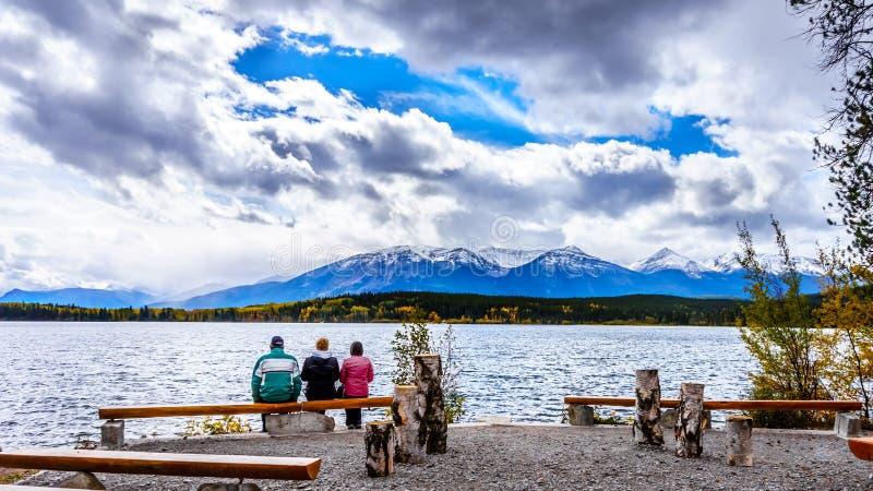 Drie Mensen die van de mening van Piramidemeer genieten met de Fluitersberg op de achtergrond in Jasper National Park stock afbeeldingen