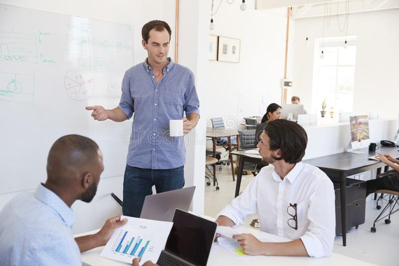 Drie mensen die zaken bespreken bij whiteboard in een bezig bureau stock foto