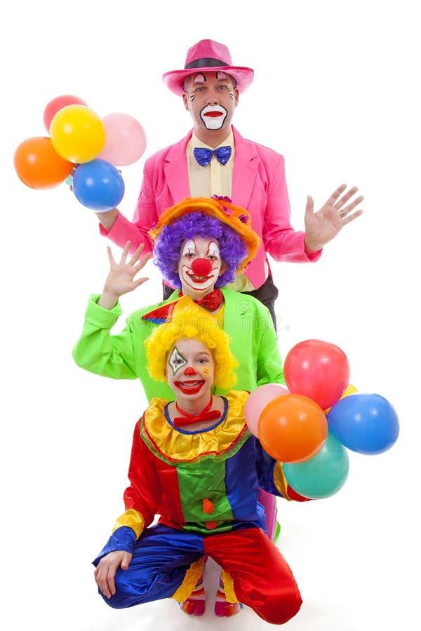 Drie mensen kleedden zich omhoog als kleurrijke grappige clowns royalty-vrije stock afbeelding
