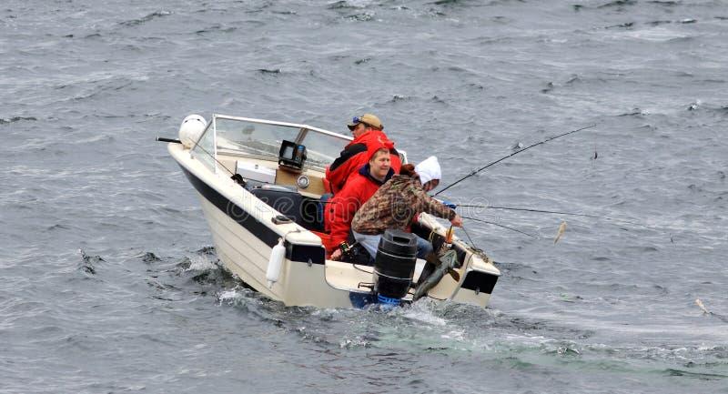 Drie Mensen in Kleine Grote Vissen BoatCatch stock afbeelding